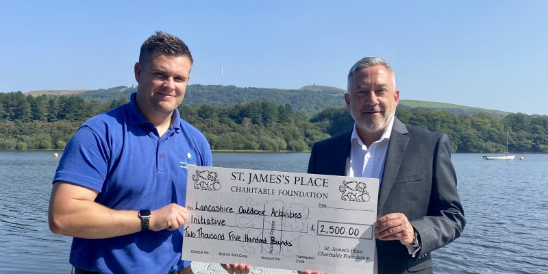 CEO David Germain receiving a cheque from Nicholas Barker handing over a cheque for £2500 to contribute towards the pontoon jetty they are stood on.