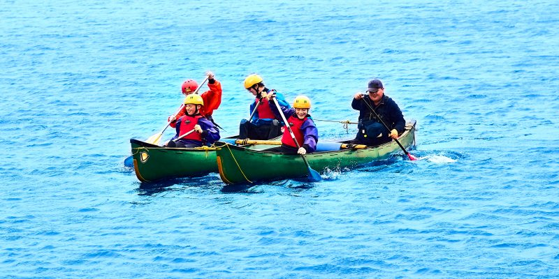 Four school boys paddling rafted canoes with their volunteer instructor Martin in High Rid reservoir. Promoting the HAF programme run by Bolton Council.