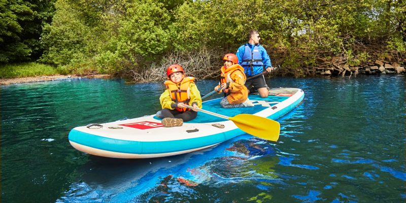 2 primary school aged girls on a giant paddleboard with their teacher on the water.